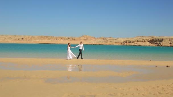 Esküvői pár sétál a tengerparton, Egyiptom. Egzotikus nászút