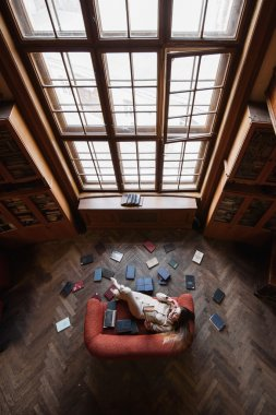 Stylish young girl in beige suit reads a book on the red sofa surrounded by books. Top view
