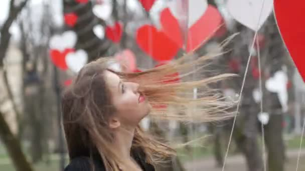 Stylish blonde girl playing with red paper hearts decoration in the autumn park. Valentines day celebration