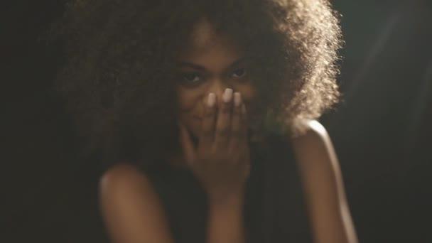 schöne exotische schüchterne junge schwarze Frau bedeckt Gesicht von Hand und flirtet