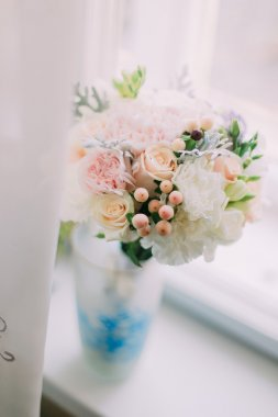 Beautiful delicate bouquet of pink and orange roses in a blue vase on the windowsill,  white interiour