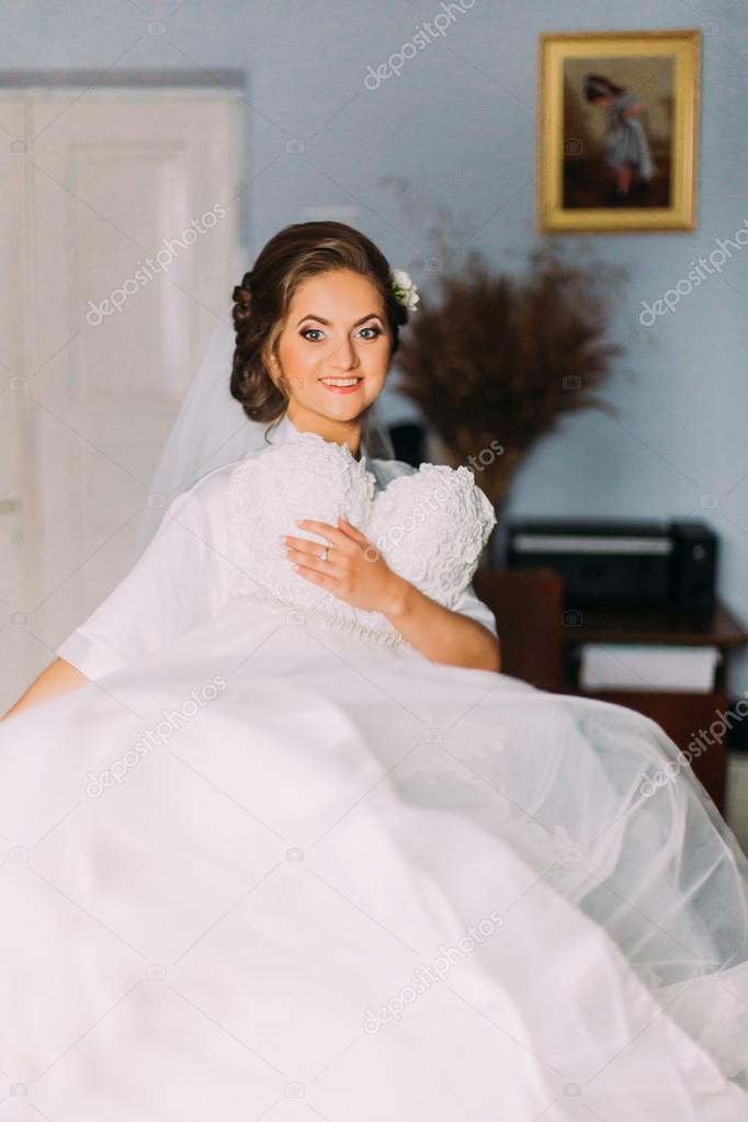 Schöne sinnliche blonde Braut in Robe und weißen Schleier posiert ...