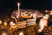 Fotografie Romantic dinner with candles, cake and wine glasses at coast against wonderful night
