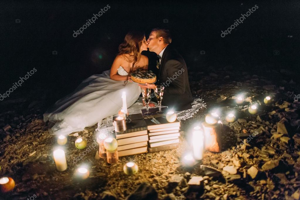 Loving couple kissing on romantic dinner with candles and cake  at beach, coast against wonderful night