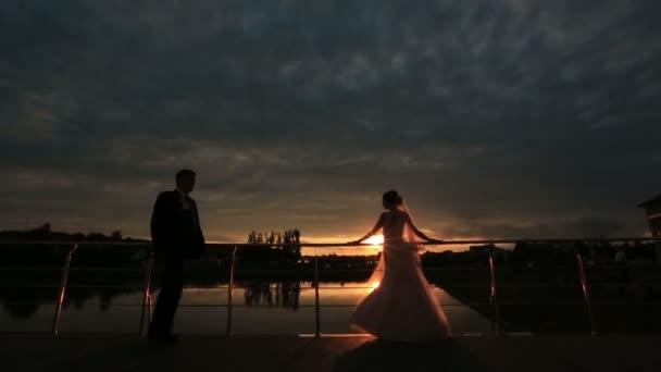 Romantický milenec objímání na twlilight s západ slunce v pozadí. Něžné chvíli lásky mezi Svatební pár