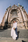 Photo Smiling newlywed couple dancing and hugging near old gothic christian cathedral