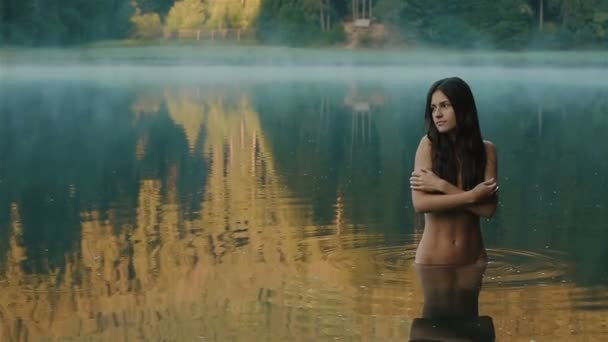 Close up of young and beautiful seductive girl mermaid with no make up and  long dark hair softly touching her skin with view of mountain Synevir lake on background. Carpathian mountains