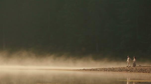 Veselý venkovský pár v ukrajinských etnických šatech, které se krátí na skalnaté pobřeží při západu slunce ve zlaté mlze u malebného horského jezera v Karpatech. Věčná harmonie mezi člověkem a přírodou