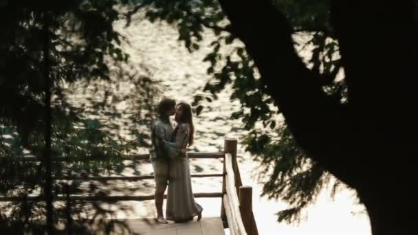 Side view of happy young couple standing on edge of pier by lake in mountains and softly embracing. Carpathians, Ukraine