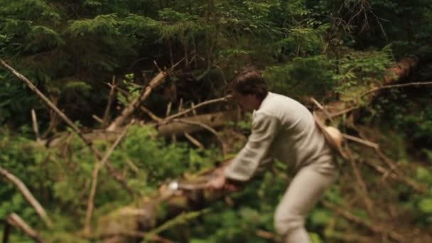 Fiatal honfitárs favágó hagyományos ukrán ruhában fát vág a Kárpátok zöld erdejében