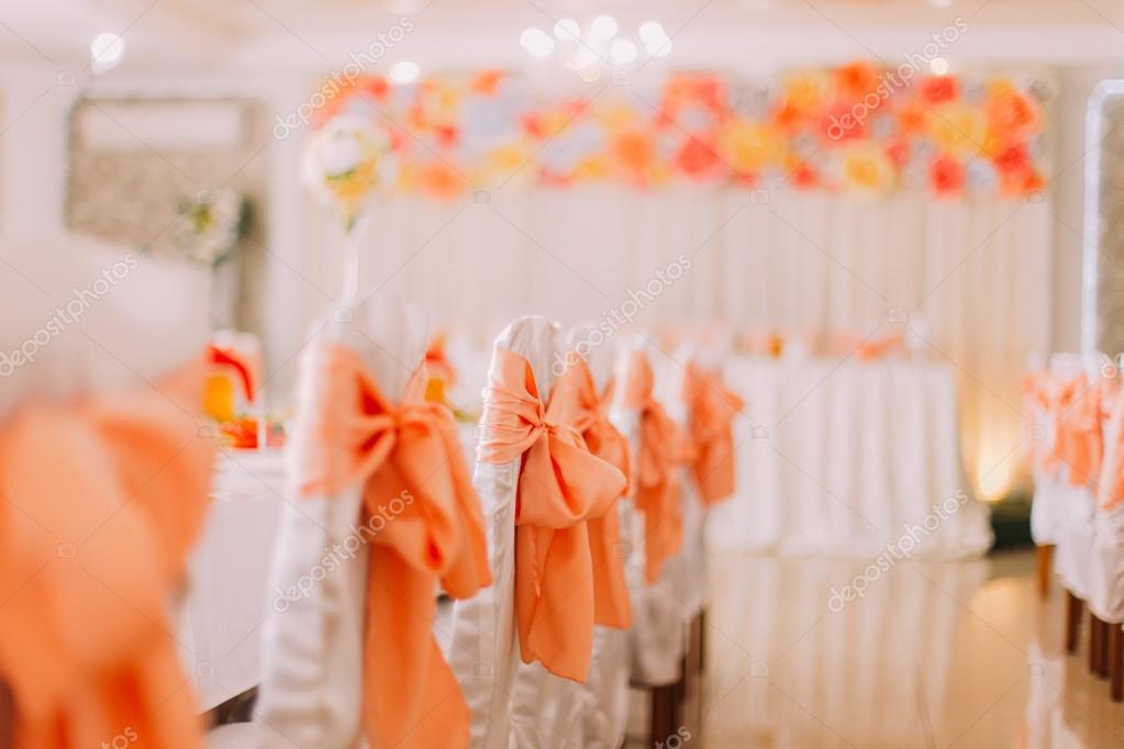 Decorazioni Matrimonio Arancione : Sedie bianche con decorazione di nastro arancione a un matrimonio