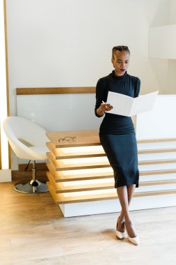 Stern elegant business woman wearing black dress and beige shoes in light office looking at her agenda, full length portrait