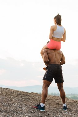 Portrait of a muscular young black african american man giving piggyback ride to his sexy girlfriend