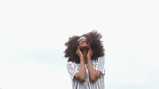 Cheerful hipster young african american woman in sunglasses listening music and smiling. Moment of joy and happiness. Sky background