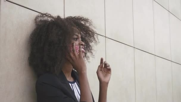Close-up of attractive african american businesswoman talking by phone and relying on the white textured wall