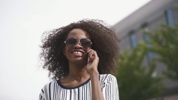 schöne fröhliche afrikanisch-amerikanische Geschäftsfrau mit Sonnenbrille, die am Telefon spricht und lächelt. Hintergrund Stadtbild