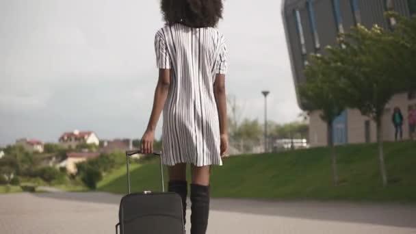 Rückansicht einer eleganten afrikanisch-amerikanischen Geschäftsfrau im stylischen kurzen Kleid, die mit ihrem Gepäck zum Flughafen fährt. Geschäftsreisekonzept