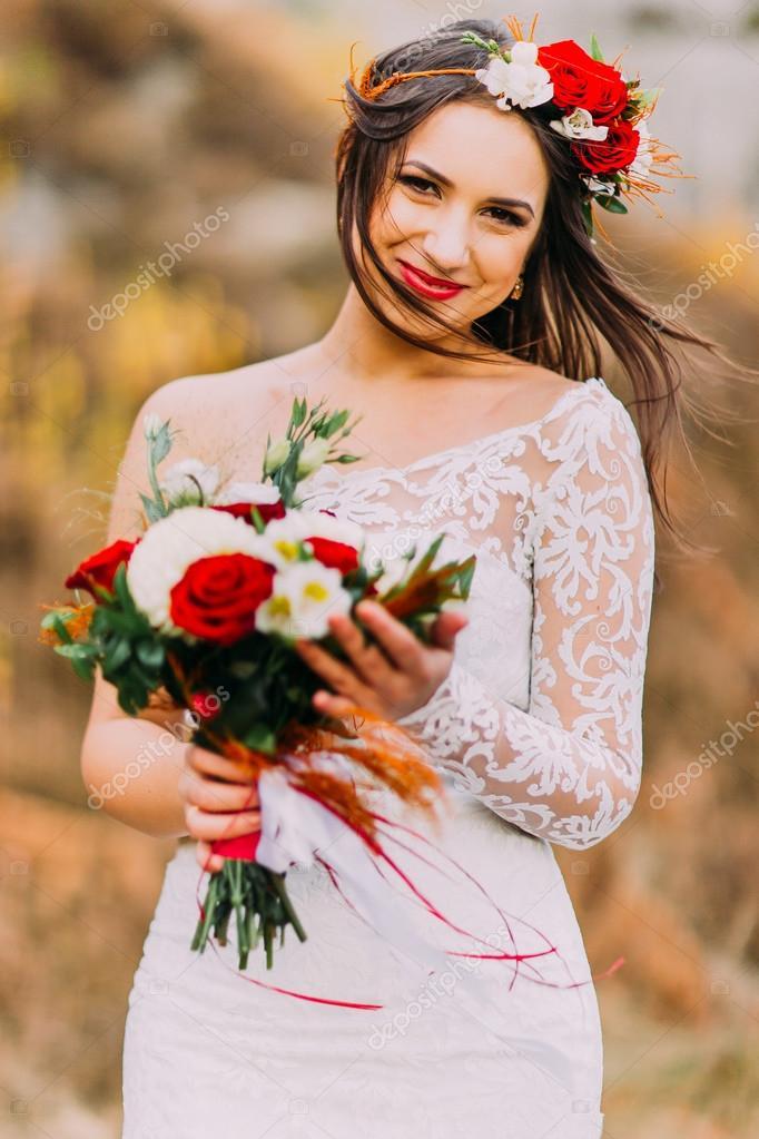 d1ec3c4016e6f Невинних романтичний красива наречена у стильному весільну сукню. Молода  дівчина з букетом червоних троянд білі та голові вінок. Природний ландшафт  як тло.