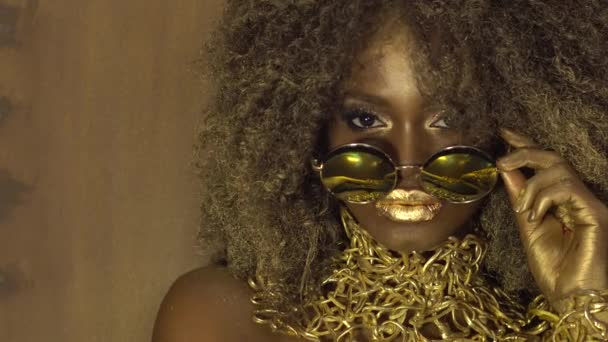 Magic surreal golden african american female model in massive sunglasses with bright glitter makeup, glossy golden hairstyle and big red lips posing on the black studio background