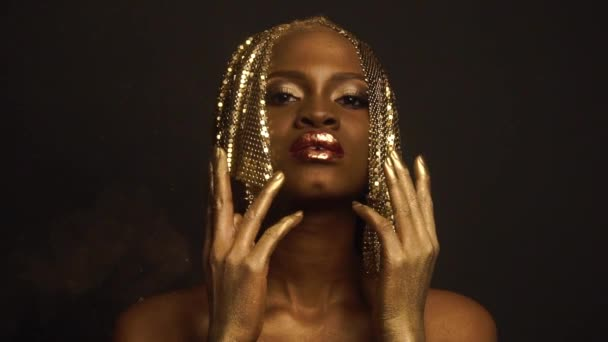 Surreal Portrait of Sexy African American Woman with Glossy Golden Makeup and Headwear Posing on Black Studio Background. Bronze Bodypaint