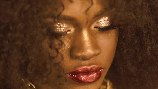 Surreal portrait of african american female model with gold glossy makeup and big red lips. Face art. Creative Vogue concept