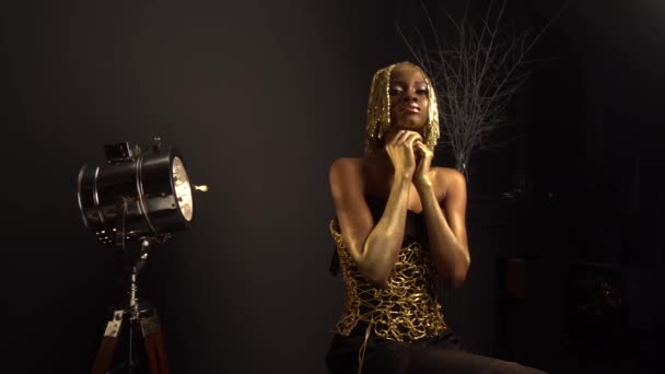 Rich luxurious portrait of sexy african american female model with glossy golden makeup and glossy headwear posing to the camera. Bronze bodypaint, black studio background