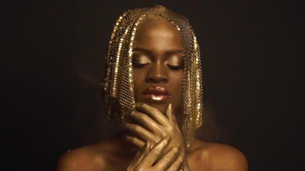 Záhadný kouzelný afroamerický model ženského pohlaví se zlatým lesklým make-upem a s pokrývkou hlavy pro kameru. Vysoký módní koncept Vogue
