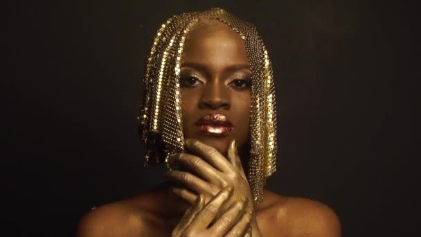 Reflexion. Portrait of glossy african american female model with bright glossy golden makeup posing on black studio background. High fashion shooting, Vogue concept