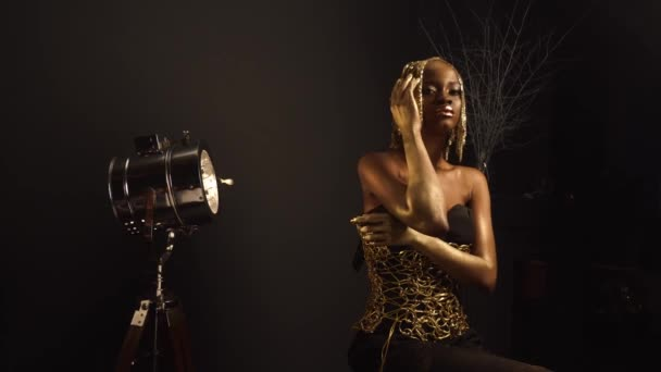 Creative luxurious portrait of sexy african american female model with glossy golden makeup and headwear posing to the Camera. Bronze bodypaint, black studio background