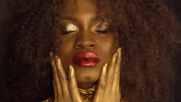 Detail módní portrét mladé afroamerické ženy modelu s zlaté lesklé make-up. Tvář umění. Černá studio pozadí
