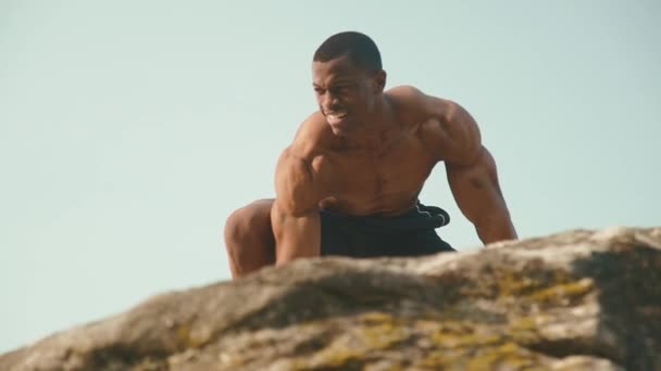 Close-up of muscular african american man bodybuilder with naked torso posing on the rocky mountain peak with blue sky background. Wild nature style.