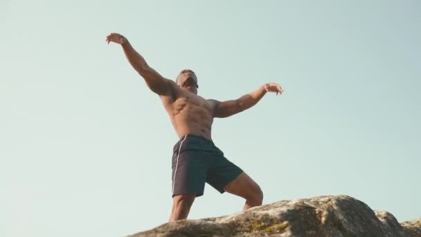 Muscular strong black bodybuilder posing on the rock against blue cloudy sky. Perfection of humans body