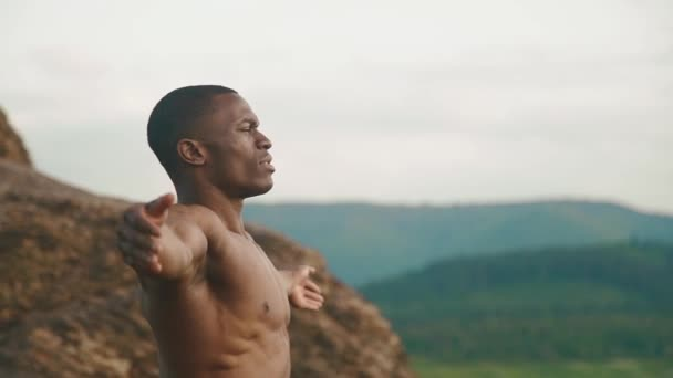 Side view of strong african american bodybuilder stretching outdoor. Mountain landscape background. Moment of harmony with nature