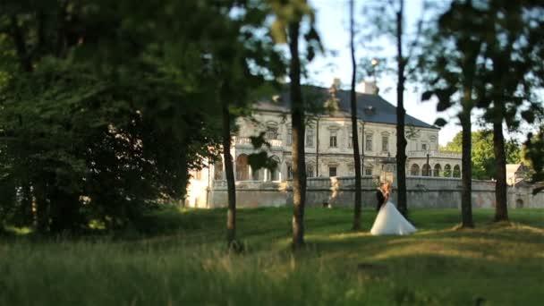 Gyönyörű fiatal esküvői pár halkan csók, zöld erdőben. A háttérben a gyönyörű reneszánsz régi kastély