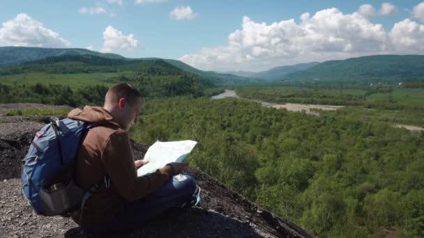 Mladý aktivní muž kontrolu krajina terén s mapou zatímco sedí na mountain rock