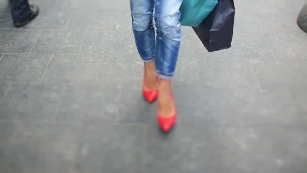 Sexy módní mladá dáma v džínách a stylové červené boty chodí na městské ulici davem