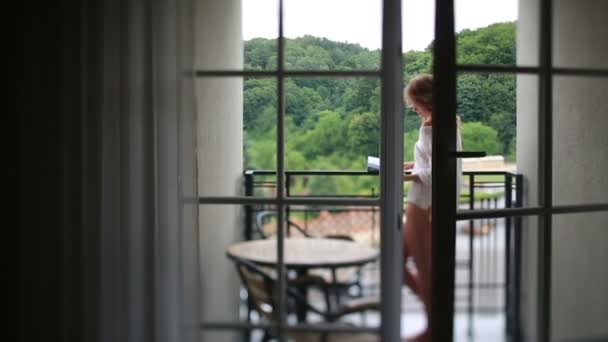 Uvolněná žena ve světle bílá halenka ve své knížce o nádherném ranní