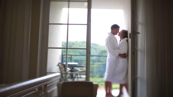 Krásný Kavkazský pár v župany objímání a líbání na balkóně