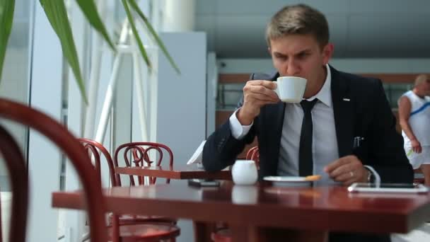 Business man talking by phone while drinking coffee, sitting in bright cafe