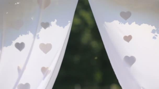 Krásné svatební oblouk dekorace detail s tkaninou srdce houpání na vítr