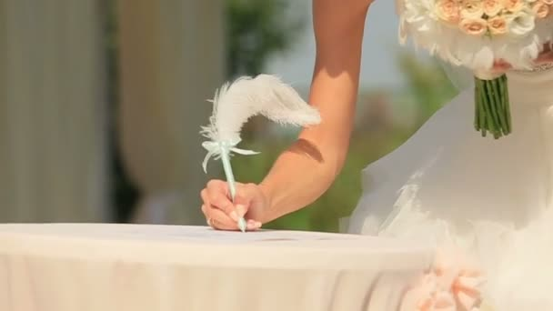 Nevěsta a ženich bere pero a podepíše certifikát svatební