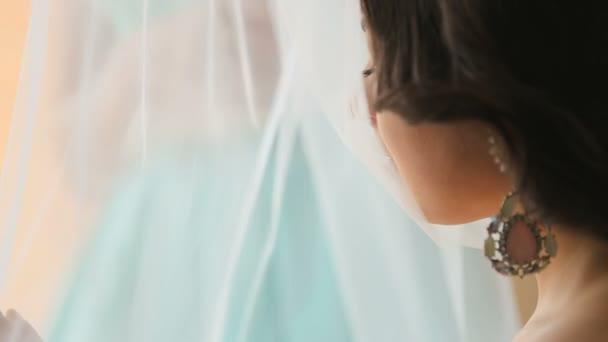 Elegantní luxusní nevěsta oblečená v elegantní bílé šaty čekají na svatební obřad a trochu nervózní