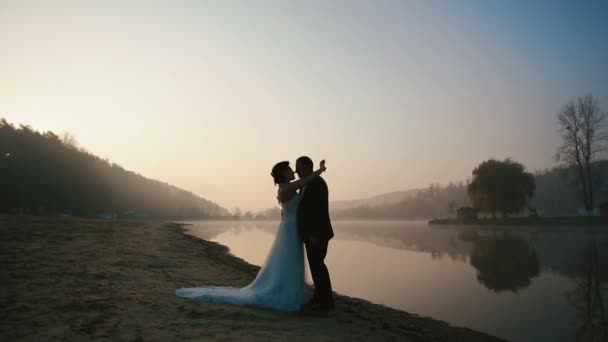 Two happy newlyweds have sweet talk and kissing at the evening of wedding day at the romantic lake on the sunset