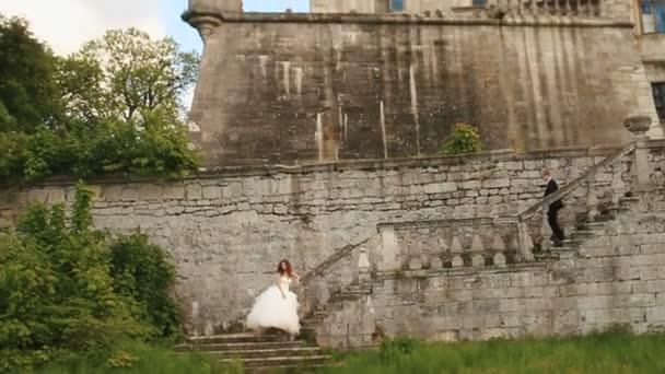 Mladá Svatební pár pózuje na starých kamenných schodech. Ruiny antické opevnění jako pozadí