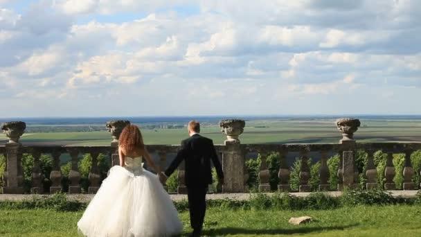 Milující ženich chodí s krásnou nevěstu na louce nedaleko staré kamenné zábradlí. Nádherná modrá obloha s velkými mraky jako pozadí