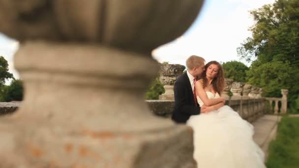 Milující ženich drží jeho krásná nevěsta na zeleném trávníku poblíž staré kamenné zábradlí a políbí jí vlasy