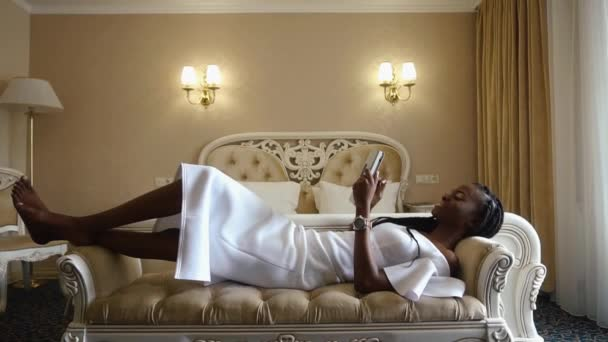 Glamorous and sexy african american lady in white cocktail dress using her tablet computer while relaxing on the sofa in luxury hotel apartments