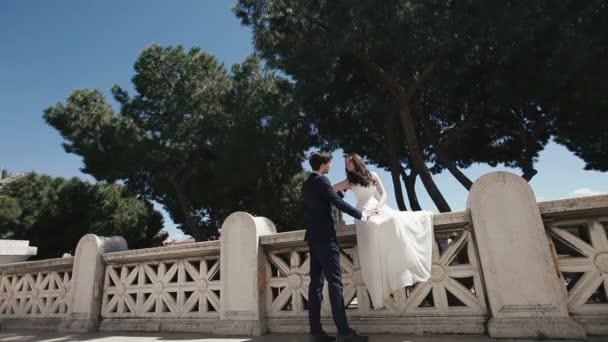 Svatební pár na romantický kamenný most v Římě. Stylový ženich líbat s krásnou nevěstu. Líbánky v Itálii, Evropa