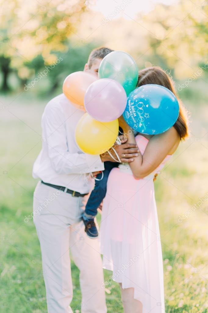 Young happy family and little son hide theis faces by colorful baloons. Green meadow on