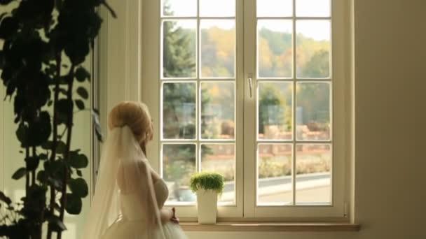 Nádherná stylová blond nevěsta při pohledu na okno a čeká na ženicha na pozadí historických prostor